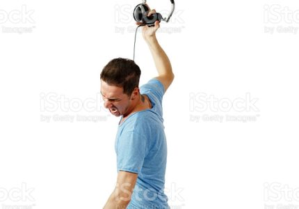Angry male with blue jeans and shirt throwing headphones
